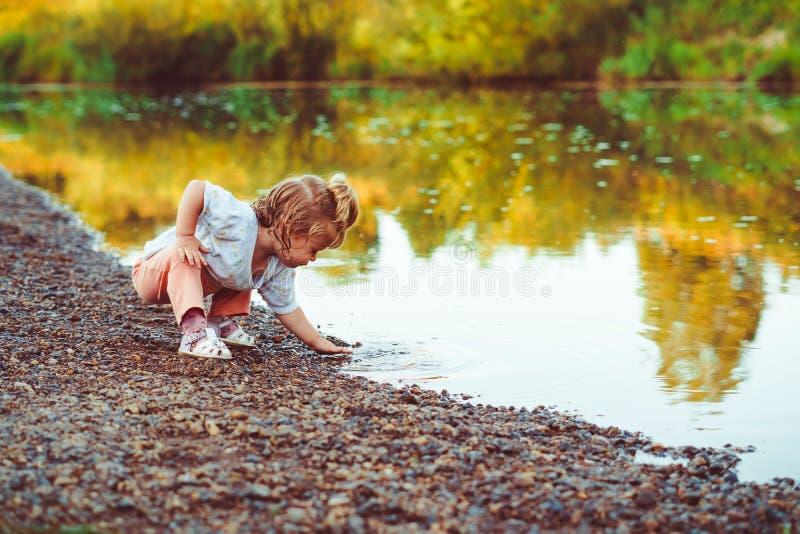 L'enfant se tient prêt la rivière photo libre de droits
