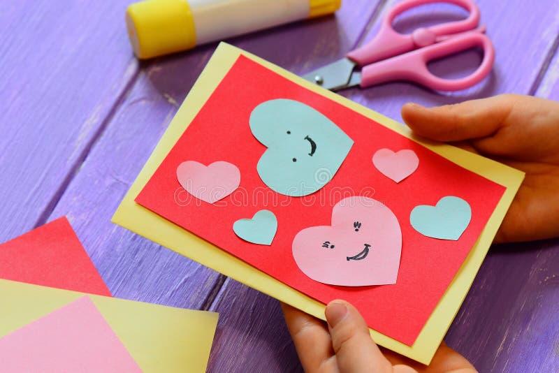 L'enfant tient une carte de valentines dans des ses mains L'enfant montre une carte de voeux Carte heureuse de jour de valentines image libre de droits