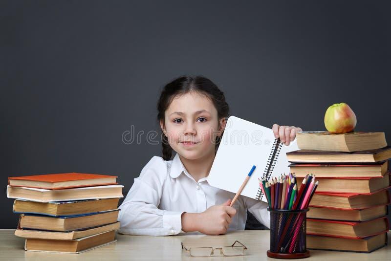 L'enfant travailleur mignon s'assied à un bureau à l'intérieur L'enfant apprend dans la classe sur le fond du tableau noir images libres de droits