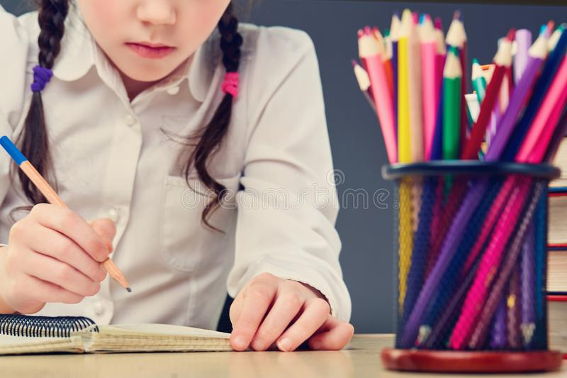 L'enfant travailleur mignon s'assied à un bureau à l'intérieur L'enfant apprend dans la classe sur le fond du tableau noir photos stock