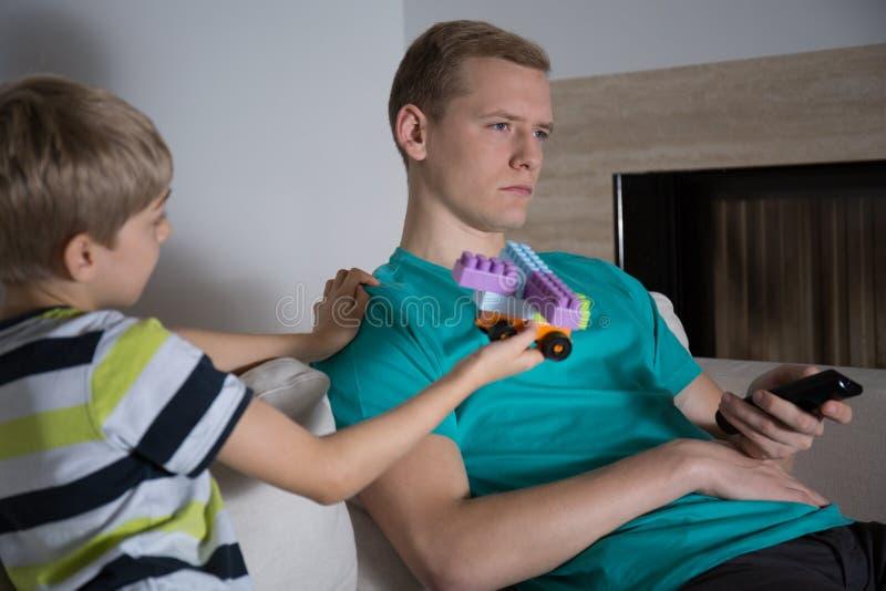 L'enfant veut jouer avec son père photo stock