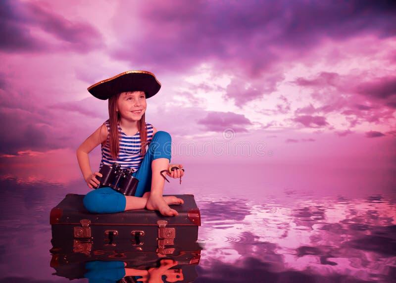 L'enfant voyage sur la mer et sur la valise photo stock