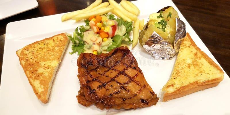 L'ensemble de bifteck de gril de poulet a fait la pomme de terre cuire au four avec du beurre, salade végétale, fait frire frança photos libres de droits