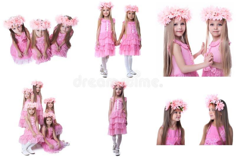 L'ensemble de petites filles adorables posent dans des robes roses photo stock