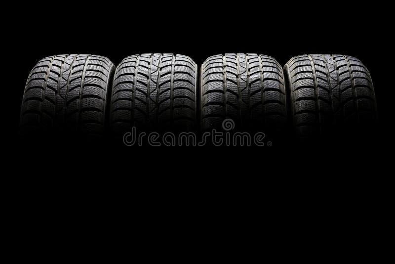L'ensemble de quatre pneus de voiture noirs a aligné horizontalement image stock