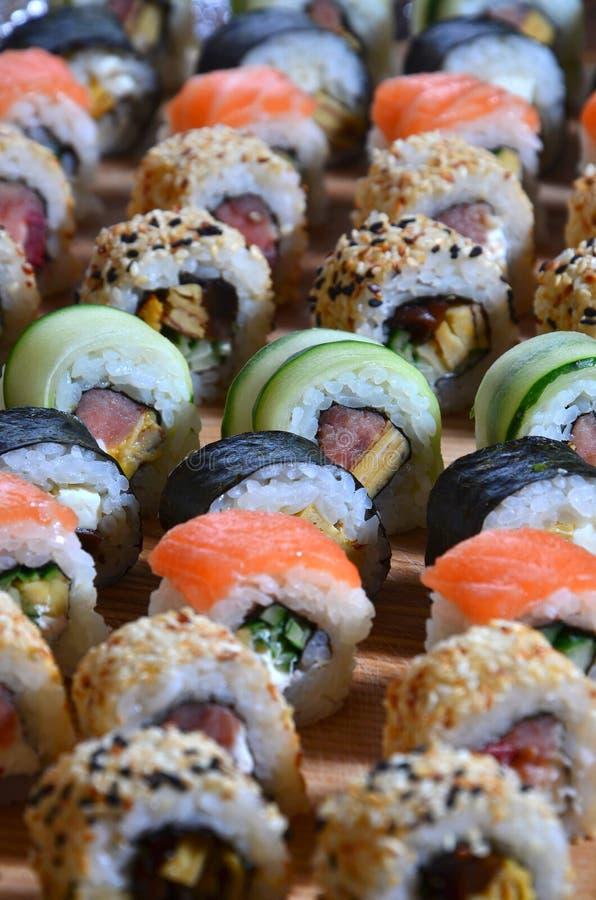 L'ensemble de sushi d'un certain nombre de petits pains est situé sur une planche à découper en bois sur une table dans la cuisin photos libres de droits