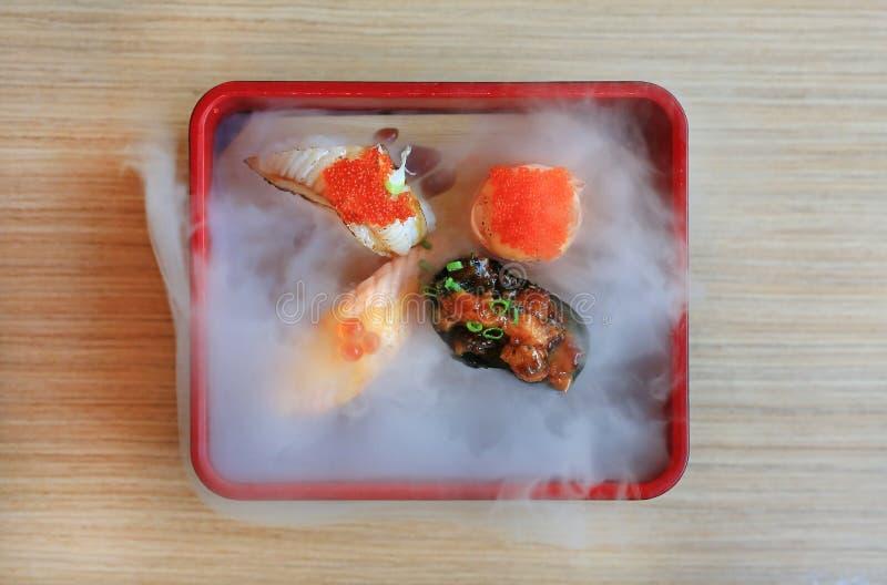 L'ensemble de sushi de Nami a servi avec froid fumé sur la table en bois traditionnel japonais de nourriture images stock