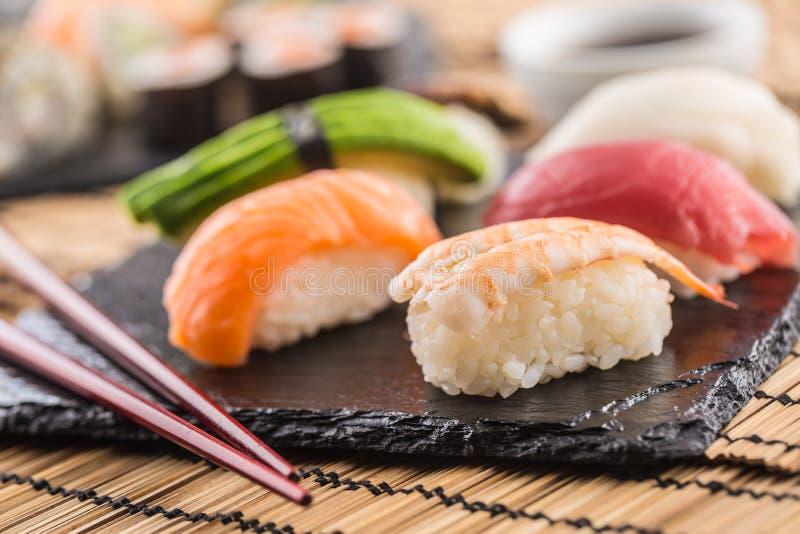 L'ensemble de sushi de nigiri sur l'ardoise embarquent avec des baguettes images libres de droits