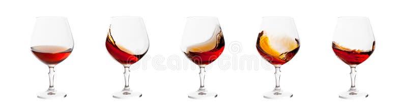 L'ensemble de verres d'eau-de-vie fine avec éclabousse d'isolement sur le blanc images stock