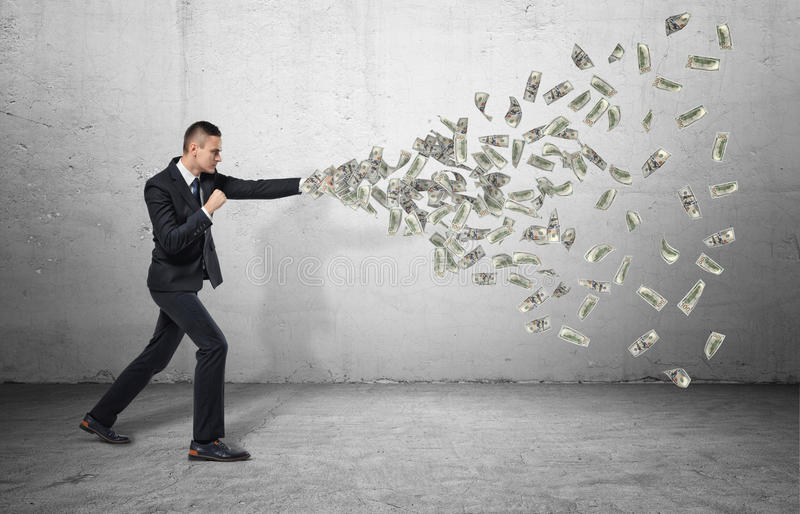 L'ente completo dell'uomo d'affari colpisce con il suoi pugno e banconote che volano da  fotografia stock