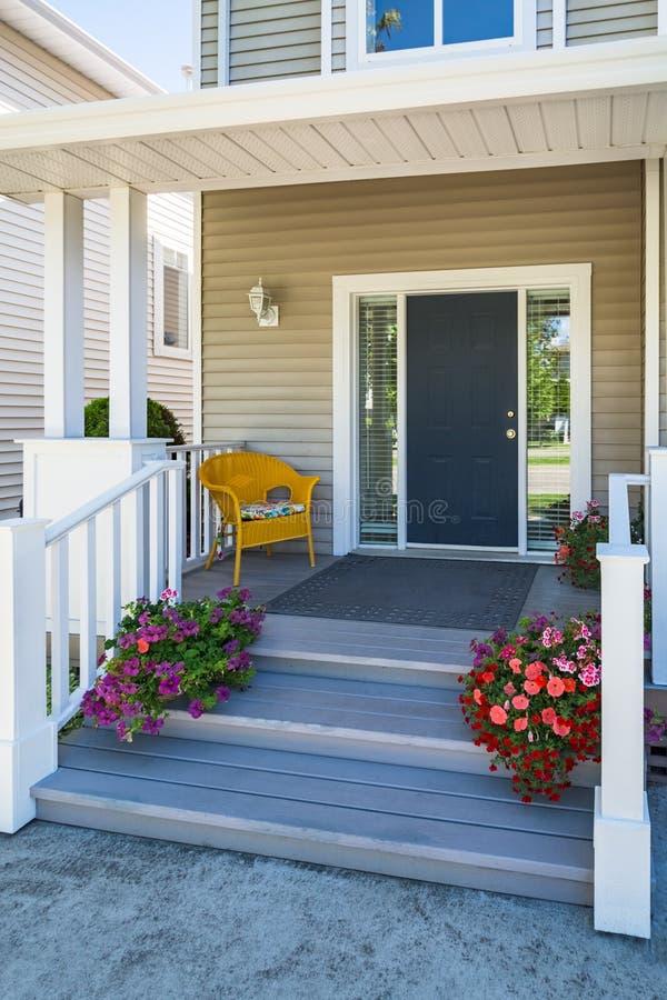 L'entrée principale de maison de famille avec la chaise jaune sous le porche et la floraison décorative fleurit image libre de droits