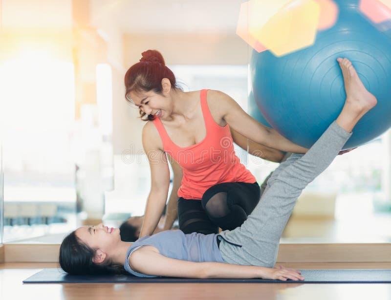 L'entraîneur asiatique de forme physique de femme enseignent son étudiant pour l'exercice en caoutchouc de boule photographie stock