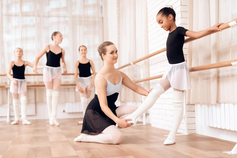 L'entraîneur ballerine d'aides d'école de ballet de la jeune exécutent différents exercices chorégraphiques photos libres de droits