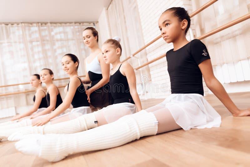 L'entraîneur ballerines d'aides d'école de ballet des jeunes exécutent différents exercices chorégraphiques photos libres de droits