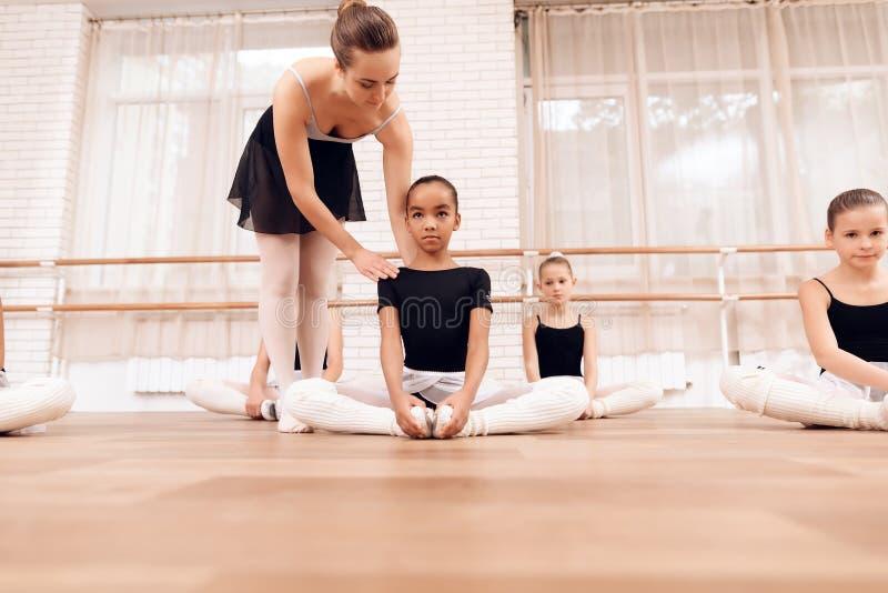L'entraîneur ballerines d'aides d'école de ballet des jeunes exécutent différents exercices chorégraphiques images libres de droits