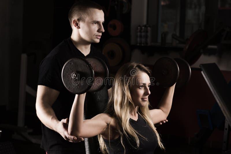 L'entraîneur de forme physique montre au client féminin comment exécuter correctement l'exercice sur le simulateur photo libre de droits