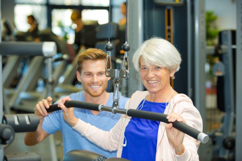 L'entraîneur de sport formant la femme supérieure avec l'étirage s'exerce photographie stock