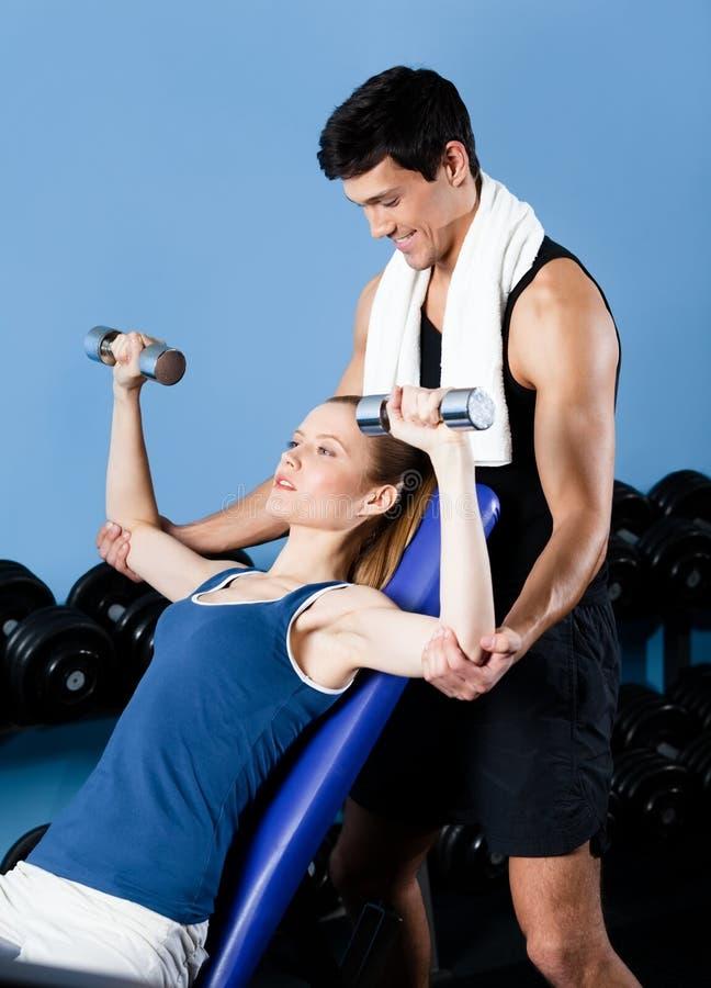 L'entraîneur de sports aide la femme à s'exercer avec des poids photos libres de droits