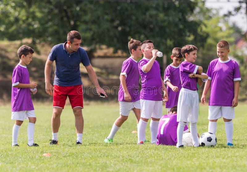 L'entraîneur donne des conseils aux footballeurs au match de football image libre de droits