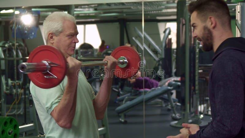 L'entraîneur donnent le barbell au client supérieur image libre de droits