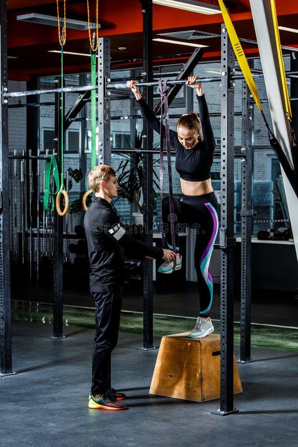 L'entraîneur enseigne à tirer vers le haut sur une fille horizontale de barl photographie stock