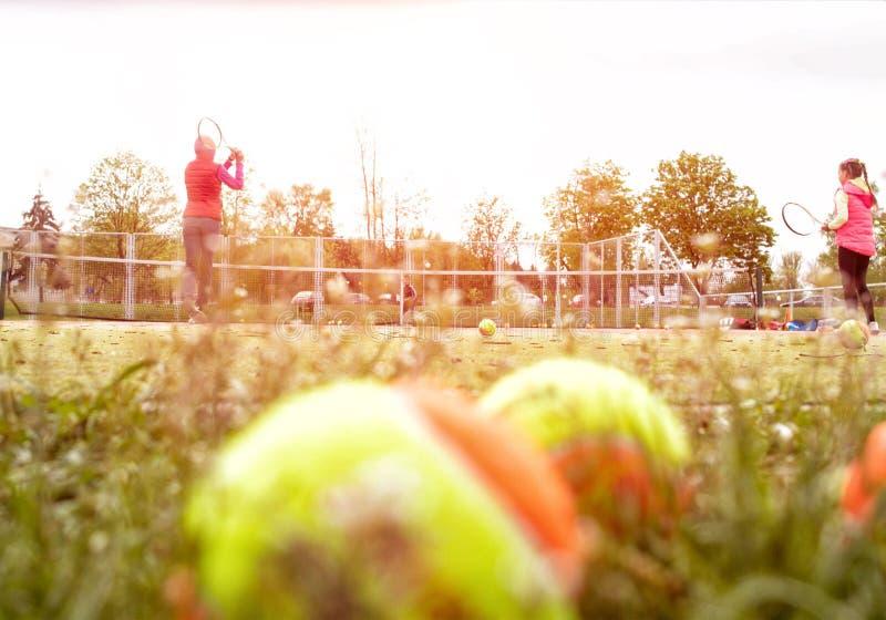 L'entraîneur enseigne la petite fille à jouer au tennis, article de sport pour jouer au tennis, l'espace de copie, extérieur images stock