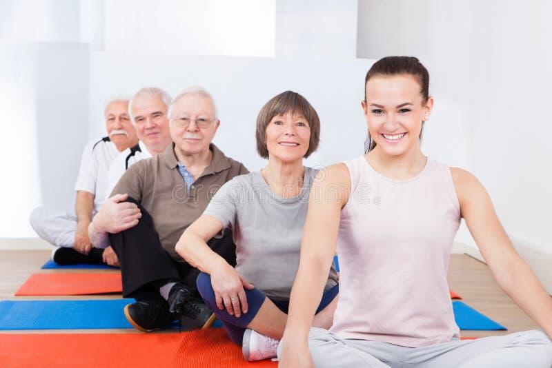 L'entraîneur et les clients supérieurs s'asseyant dans le yoga classent photo stock