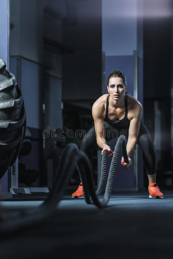L'entraîneur musculaire attirant puissant de CrossFit luttent la séance d'entraînement avec des cordes photos libres de droits