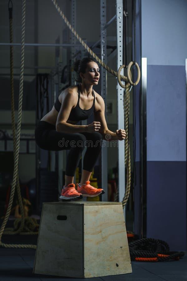 L'entraîneur musculaire puissant de CrossFit de femme saute pendant la séance d'entraînement au gymnase image stock