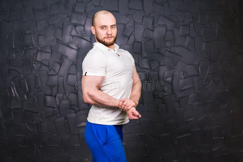 L'entraîneur personnel de forme physique pose sur le fond gris photos libres de droits