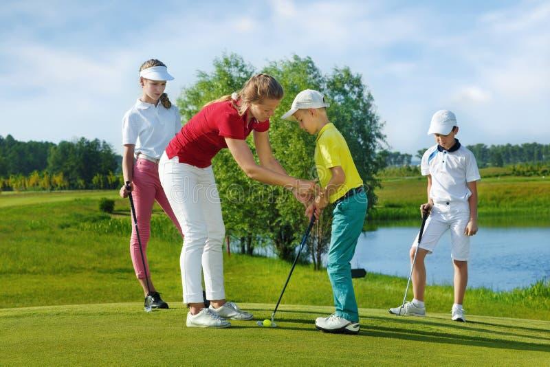 L'entraîneur travaille avec des enfants à l'école de golf image libre de droits
