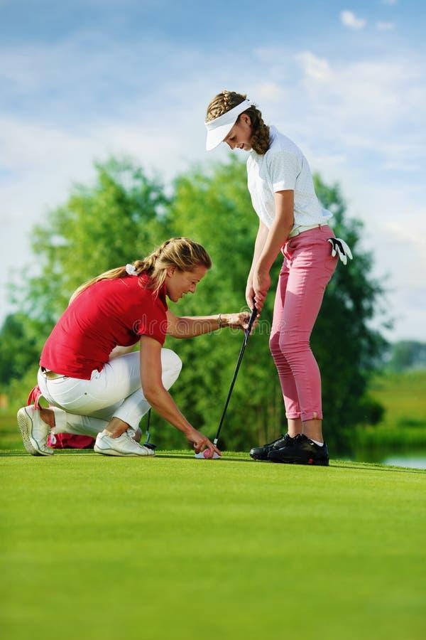 L'entraîneur travaille avec des enfants à l'école de golf images stock
