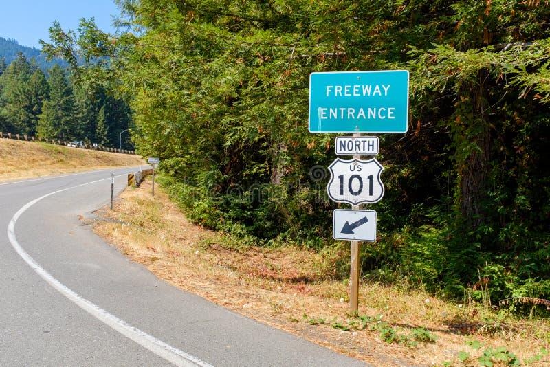 L'entrata dell'autostrada senza pedaggio firma dentro un'abetaia immagini stock
