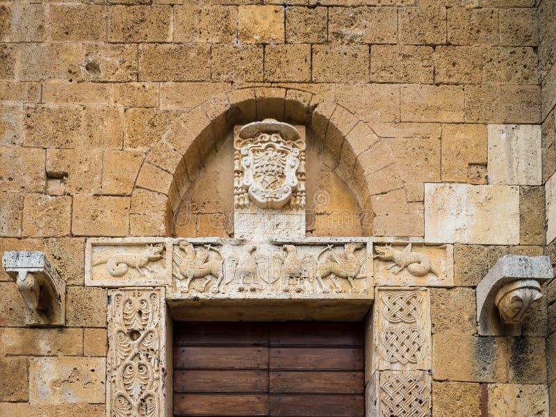 L'entrata di pietra scolpita di una chiesa medievale italiana antica immagine stock