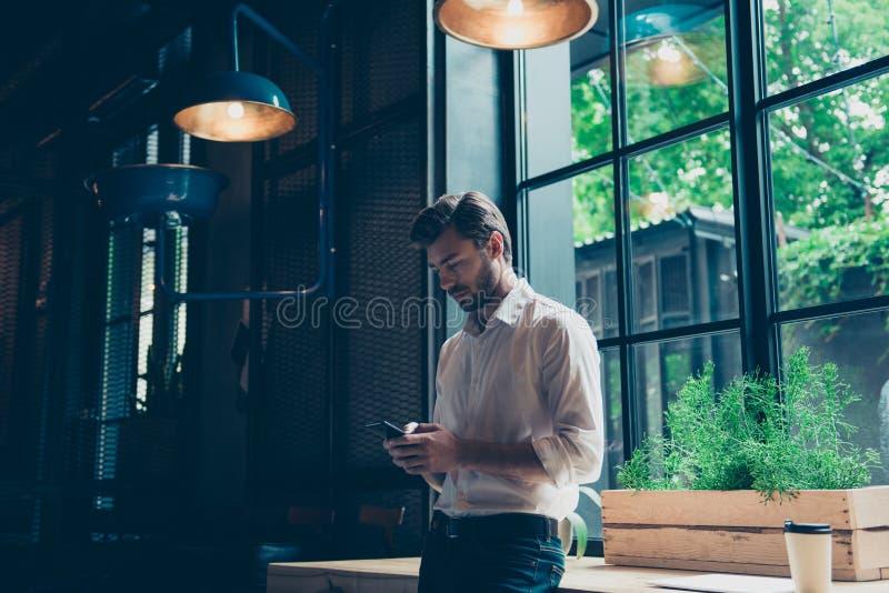L'entrepreneur bien habillé de jeunes passe en revue à son téléphone portable au bureau moderne, est derrière une fenêtre, il est image libre de droits