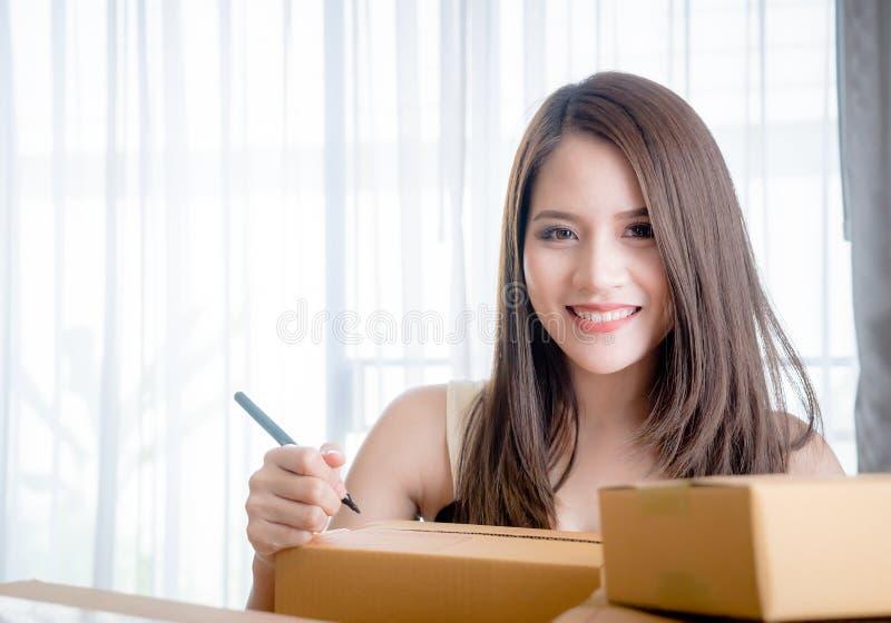 L'entrepreneur en ligne écrit l'adresse sur des boîtes pour envoyer à la maison de client photo libre de droits