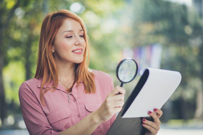 L'entrepreneur féminin observe des diagrammes avec la loupe images stock