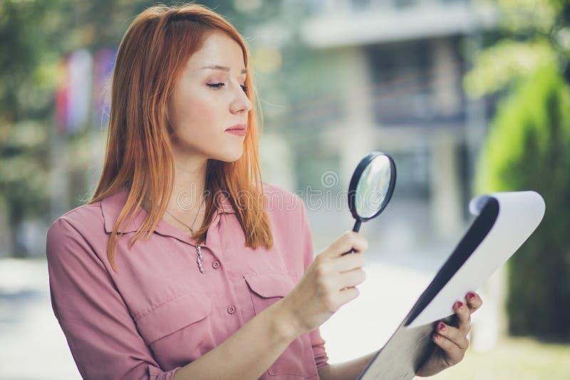 L'entrepreneur observe des diagrammes avec la loupe photographie stock