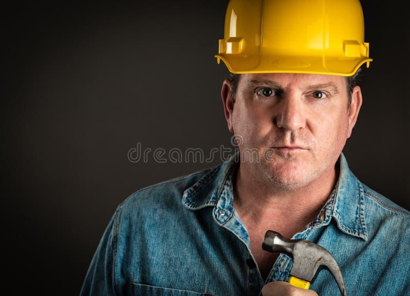 L'entrepreneur sérieux dans le casque antichoc tient le marteau avec l'éclairage dramatique photographie stock libre de droits