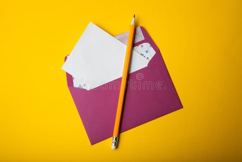 L'enveloppe avec la lettre vide sort sur un fond jaune avec l'espace de copie pour un certain texte photos stock