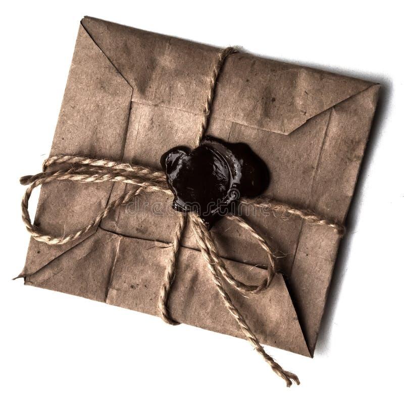L'enveloppe du papier grunge avec le joint de cire sur le blanc a isolé le fond concept des livraisons postales photographie stock