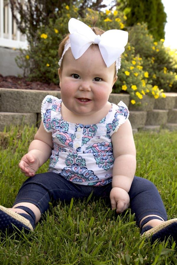 L'erba del bambino si siede il sorriso fotografia stock libera da diritti