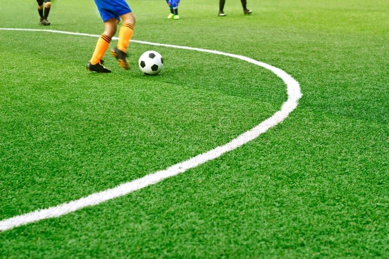 L'erba verde del campo di calcio con la linea bianca del segno ed i ragazzi giocano a calcio immagine stock