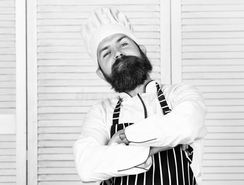 ?l es campe?n en la cocina Uniforme blanco del cocinero fuerte barbudo confiado Cocinero convertido en el restaurante Cocinero pr foto de archivo