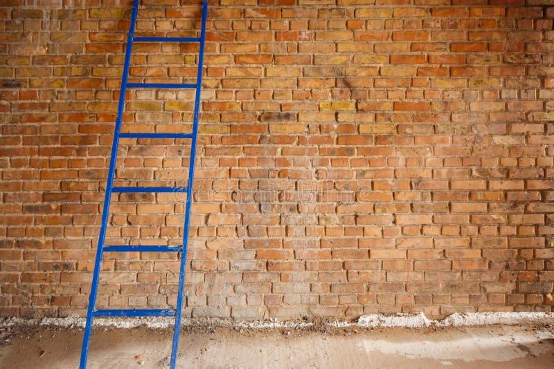 L'escalier bleu s'est penché contre le mur de la brique rouge photographie stock