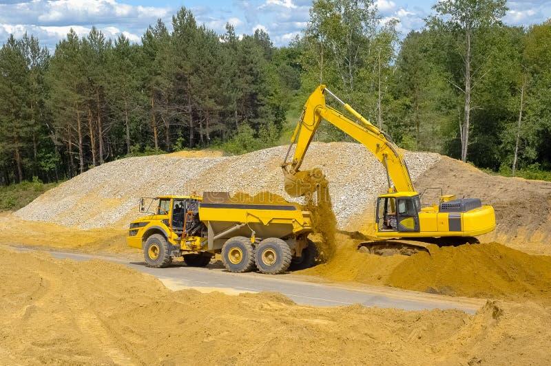 L'escavatore carica un corpo del camion con la sabbia immagini stock libere da diritti