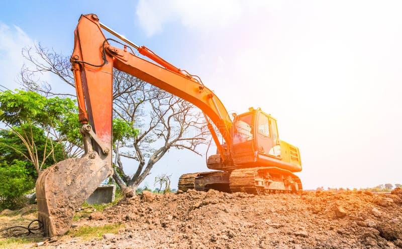 L'escavatore a cucchiaia rovescia arancio è sulla terra fotografie stock libere da diritti