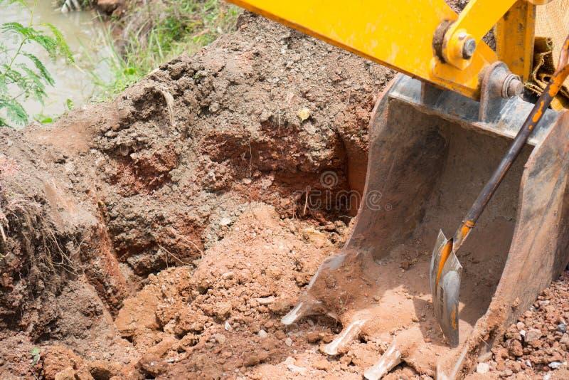 L'escavatore a cucchiaia rovescia giallo del camion sulla strada con il bei cielo ed azienda agricola fotografie stock libere da diritti