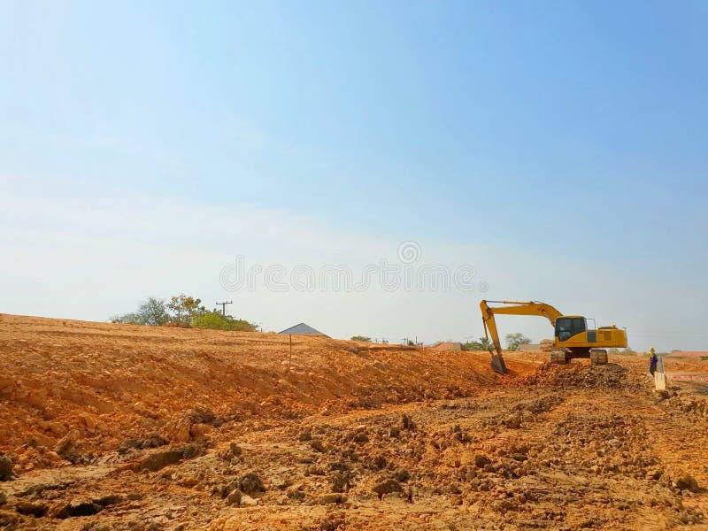 L'escavatore a cucchiaia rovescia stava scavando un pozzo su cielo blu come fondo fotografie stock