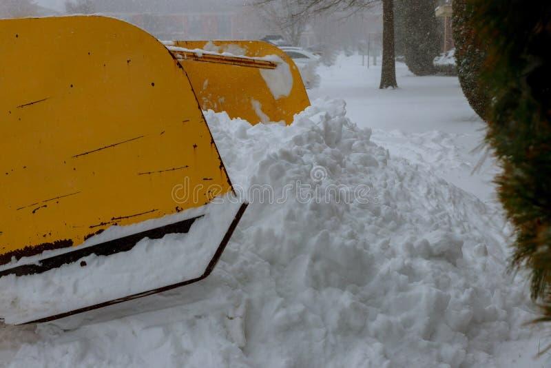 L'escavatore pulisce le vie di un gran numero di neve in città Orario invernale fotografia stock